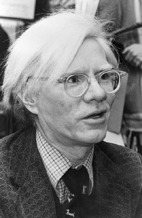 Portrait of American pop artist and filmaker Andy Warhol signs copies of his book