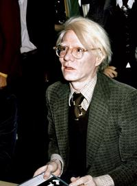 American pop artist and filmaker Andy Warhol signs copies of his book