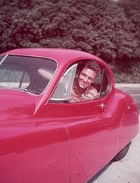 Robert Stack picture taken at the drivers seat of a red automobile in this photo from circa 1955.