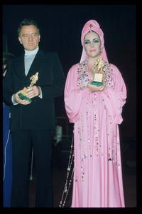 Richard Burton and Elizabeth Taylor hold award statuettes in Italy.