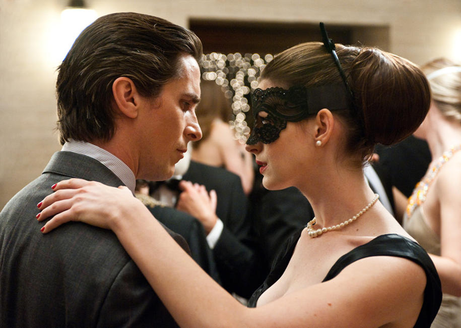 Christian Bale as Bruce Wayne and Anne Hathaway as Selina Kyle in