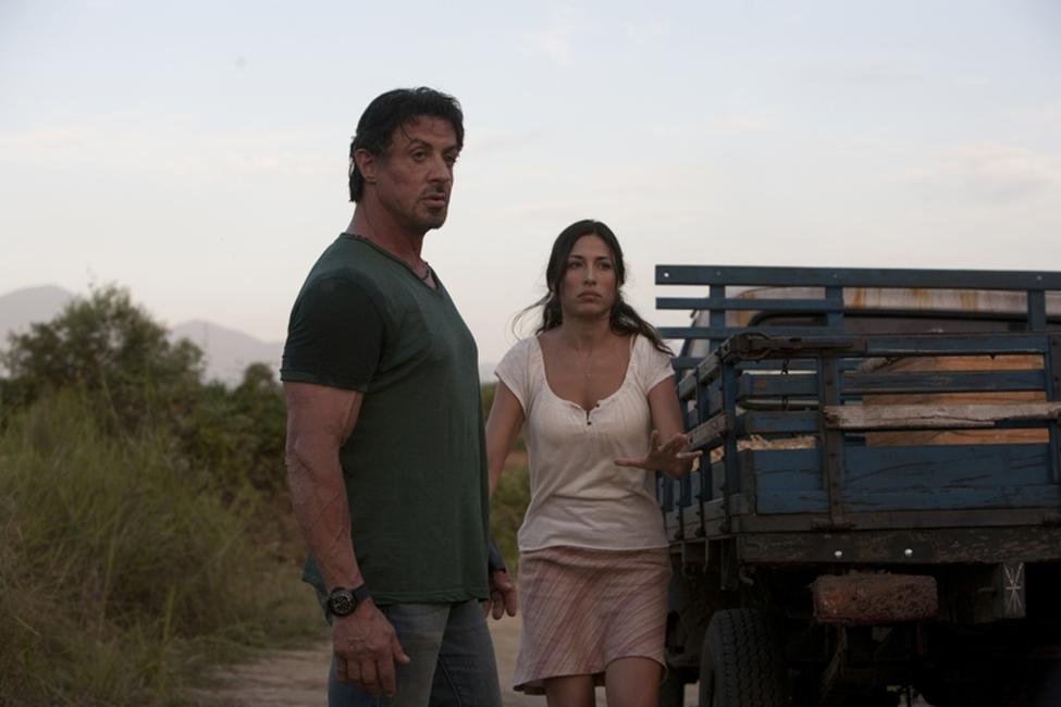 Sylvester Stallone as Barney Ross and Giselle Itie as Sandra in