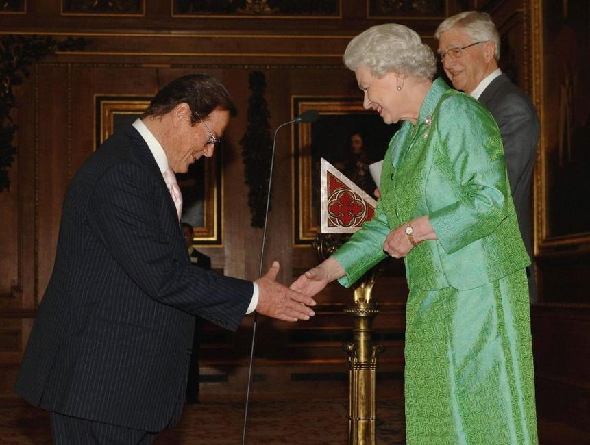 Roger Moore is greeted by Queen Elizabeth II at the Help the Aged