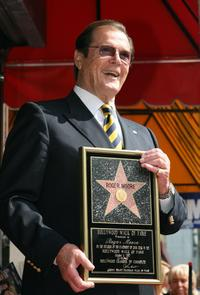 Roger Moore poses after being honored with a Star on the Hollywood Walk of Fame.
