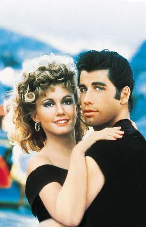 "Olivia Newton-John as Sandy Olsson and John Travolta as Danny Zuko in ""Grease Sing-a-long (2010)."""