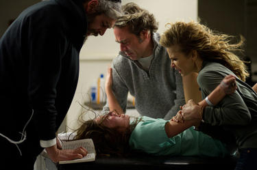 "Matisyahu as Tzadok, Natasha Calis as Em, Jeffrey Dean Morgan as Clyde and Kyra Sedgwick as Stephanie in ""The Possession."""