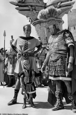 Charlton Heston (left) on the film's set in Rome with his three-year old son Fraser (center). Co-star Jack Hawkins (right) is shown chatting with Heston and his son during a break from filming.