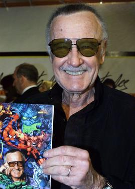 Stan Lee holds up a program honoring his 60th Anniversary.