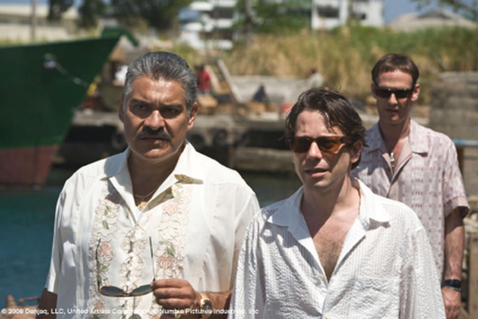 General Modrano (Joaquin Cosio), Dominic Greene (Mathieu Amalric) and Elvis (Anatole Taubman) discuss business at the Kings Quay, Haiti in