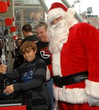 Jansen Panettiere and Santa Clause at the Ridemakerz unveiling of a toy Mini to the Boys and Girls Club.