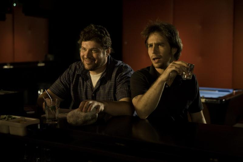 Brad William Henke as Denny and Sam Rockwell as Victor Mancini in