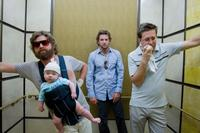 Zach Galifianakis as Alan holds Baby Tyler, Bradley Cooper as Phil and Ed Helms as Stu in