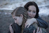 Jennifer Lawrence as Katniss Everdeen and Willow Shields as Primrose Everdeen in