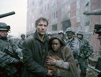 Theo (Clive Owen) protects the pregnant Kee (Clare-Hope Ashitey) in