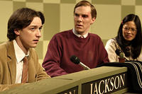 Patrick (Benedict Cumberbatch) and Lucy (Elaine Tan) give Brian (James McAvoy) a look of disgust after the answer he gives on a quiz show in