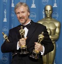 James Cameron at the 70th Annual Academy Awards holds the three Oscars he won for Best Film, Best Director, and Best Editing.