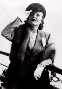 Marlene Dietrich salutes from the deck of a boat.
