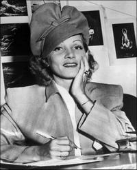 Marlene Dietrich signs her naturalization certificate for American Citizenship.