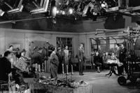 Director Alfred Hitchcock rehearses his cast as the various technicians look on.