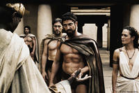 Leonidas (Gerard Butler) warns the Persian Messenger (Peter Mensah) as Captain (Vincent Regan) and Gorgo (Lena Headey) look on in