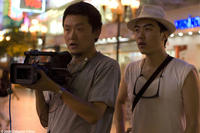 Director Yung Chang (right) and Director of Photography Wang Shi Qing on location in Liberty Square in Chongqing City for UP THE YANGTZE, a film by Yung Chang, a Zeitgeist Films release.